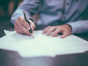 Hand mit Kugelschreiber zur Unterschrift auf Dokument